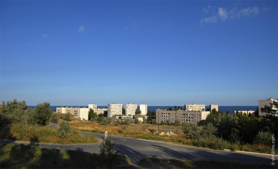 Щелкино. Слева направо дома - 99 (5-этажный, двухкорпусный), дома в кустах пропускаем, далее идут 9 этажные башни 105а, 105 и 98 (стоит боком). Потом, 5 этажный дом 93. За ним виднеется 9-этажный дом 94.